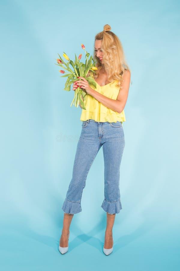 Floristics, ferier och folkbegrepp - härlig blond innehavgrupp för ung kvinna av tulpan på blå bakgrund arkivfoto