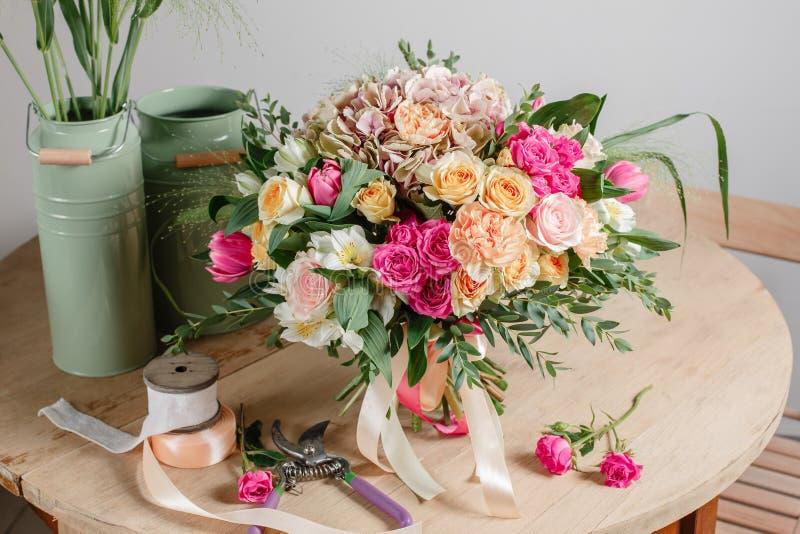 Floristischer Hintergrund der Weinlese, bunte Rosen, antike Scheren und ein Seil auf einem alten Holztisch stockfotografie