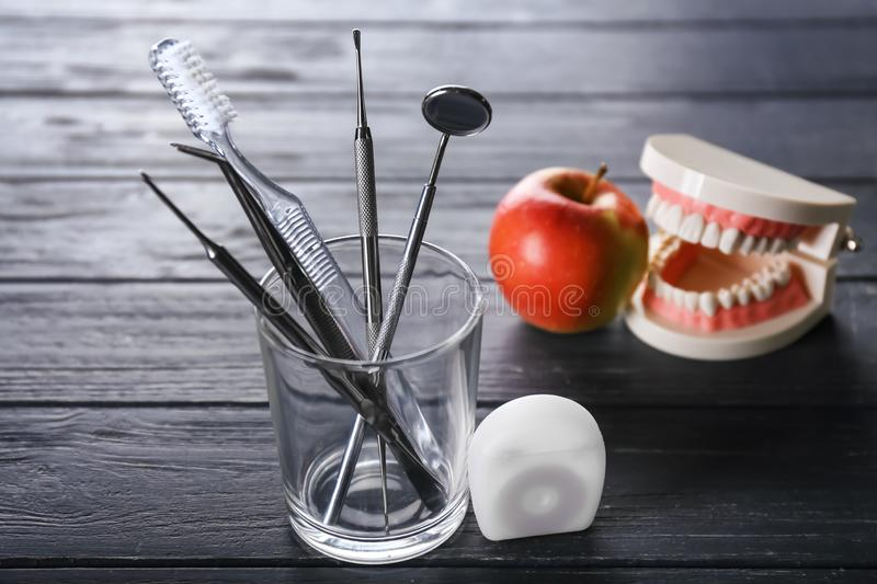 Floss, glass with toothbrush and dental instruments on dark wooden table stock photos