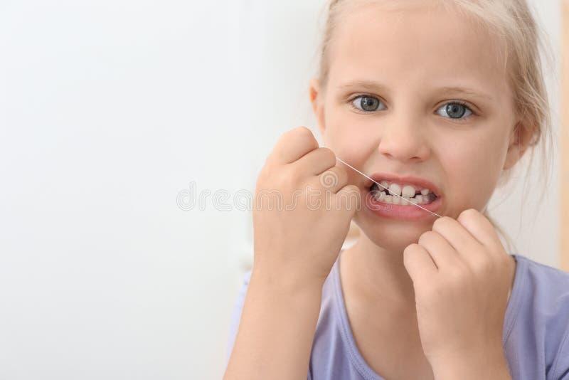 Flossing δόντια μικρών κοριτσιών στο λουτρό στοκ φωτογραφία