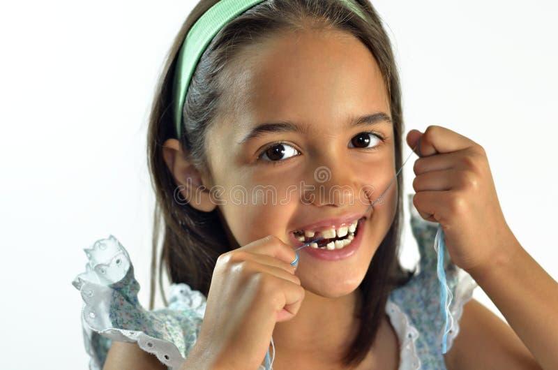 flossing flicka henne lilla tänder arkivbild