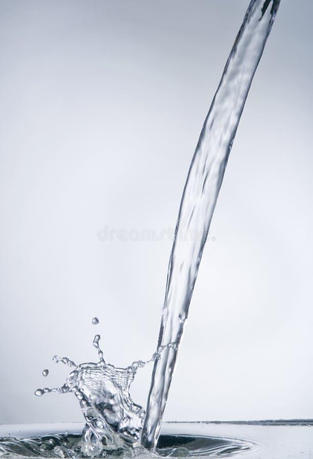 Flot de l'eau avec l'éclaboussure sur le bleu images stock