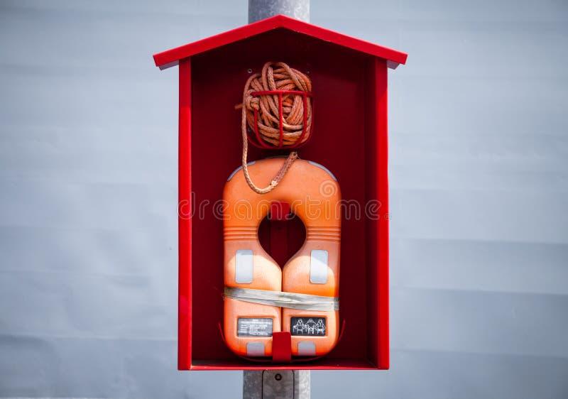 Flotador más lifevest anaranjado de una cabina roja imagenes de archivo