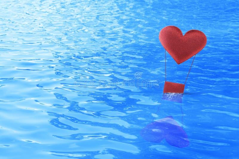 Flotador rojo del balón de aire del corazón de la tela en el mar imagen de archivo libre de regalías