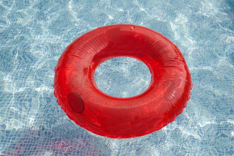 Flotador rojo que flota en la piscina imágenes de archivo libres de regalías