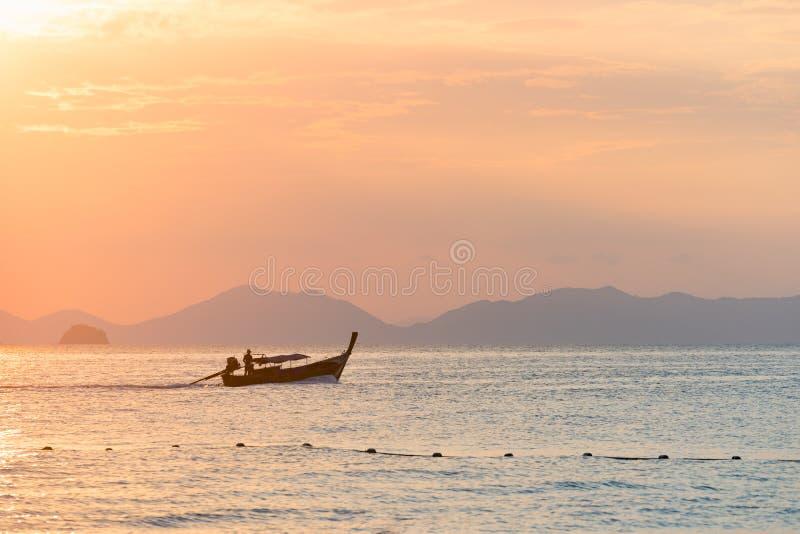 Flotadores tradicionales de cola larga tailandeses del barco en una puesta del sol coloreada hermosa en el mar contra la silueta  fotografía de archivo