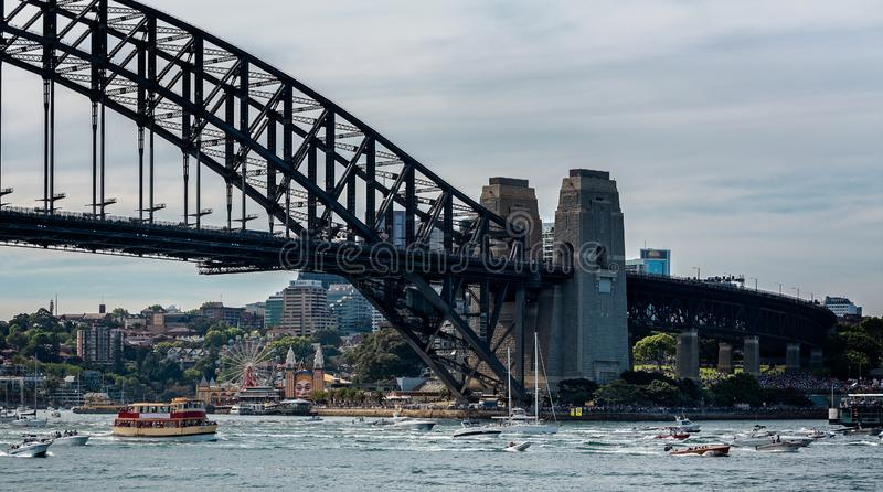 Flotilla of small boats passing under Sydney Harbour Bridge royalty free stock photography