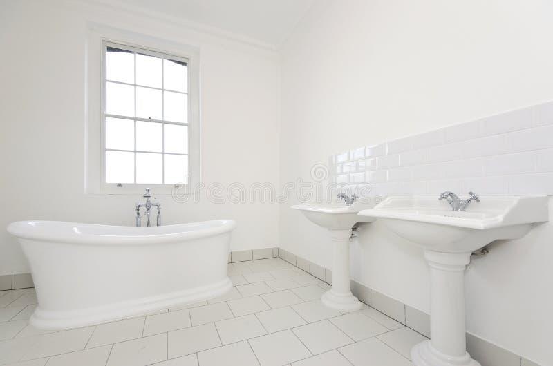 Flott familjbadrum med det fria plattform badkaret arkivbild