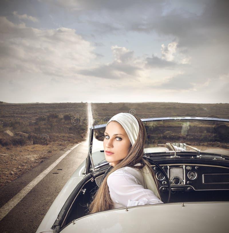 Flott kvinna i en tappningbil arkivbilder