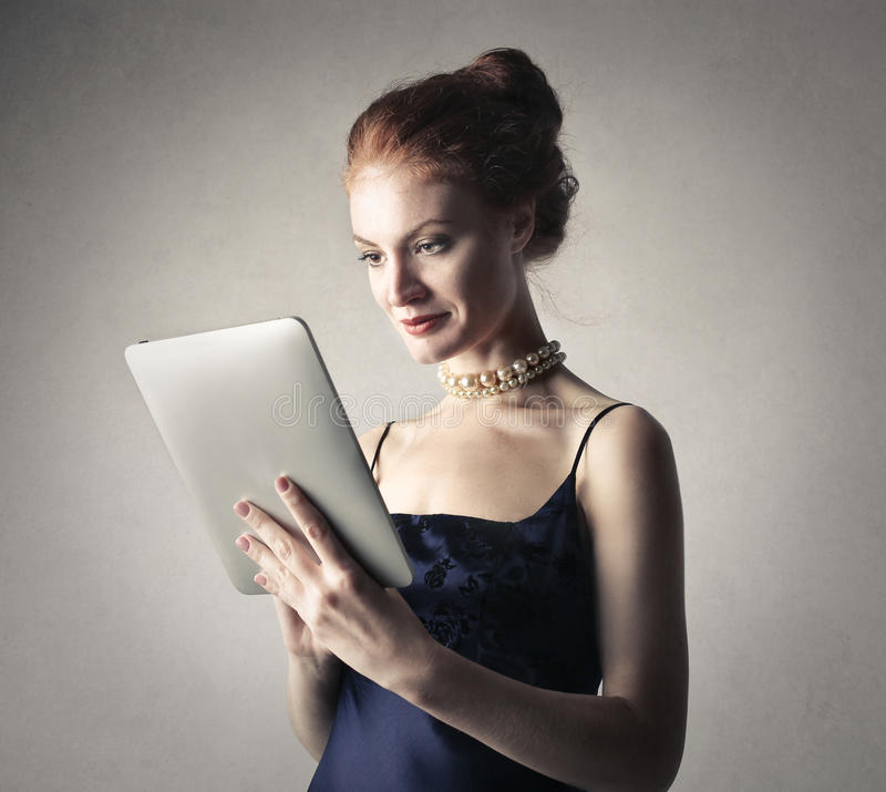 Flott kvinna som använder en minnestavla royaltyfri foto