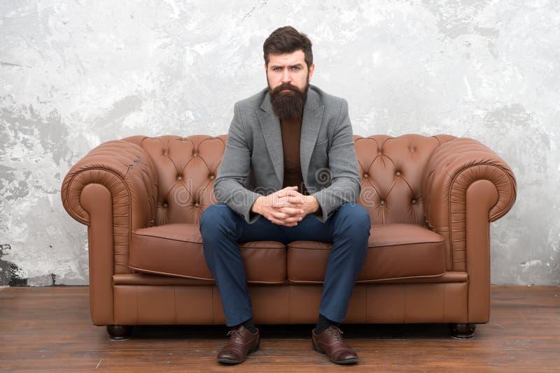 Flott men tillfälligt Skäggig man som kopplar av på soffan Man eller affärsman som bär den informella dräkten Modeman med det lån arkivbilder