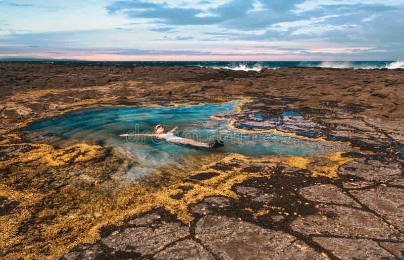 Flottement insouciant femelle dans une piscine de roche par l'océan images libres de droits