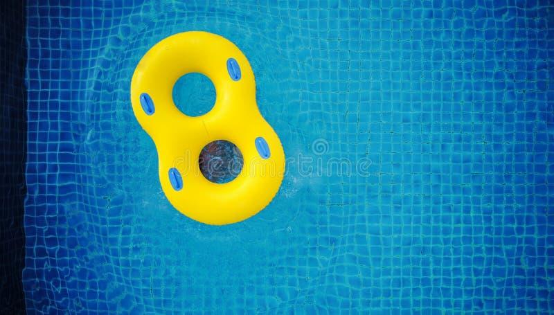 Flotteur jaune de bain, flottant sur la piscine photo stock