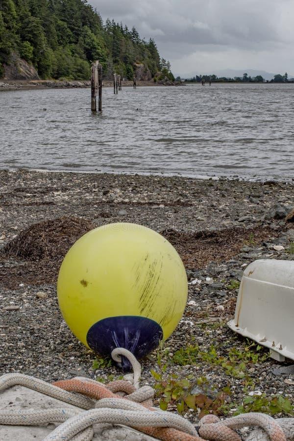 Flotteur jaune sur le rivage de la baie de Samish image stock