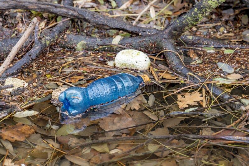 Flotteurs en plastique de bouteille de boisson sur un cours d'eau avec d'autres déchets images libres de droits