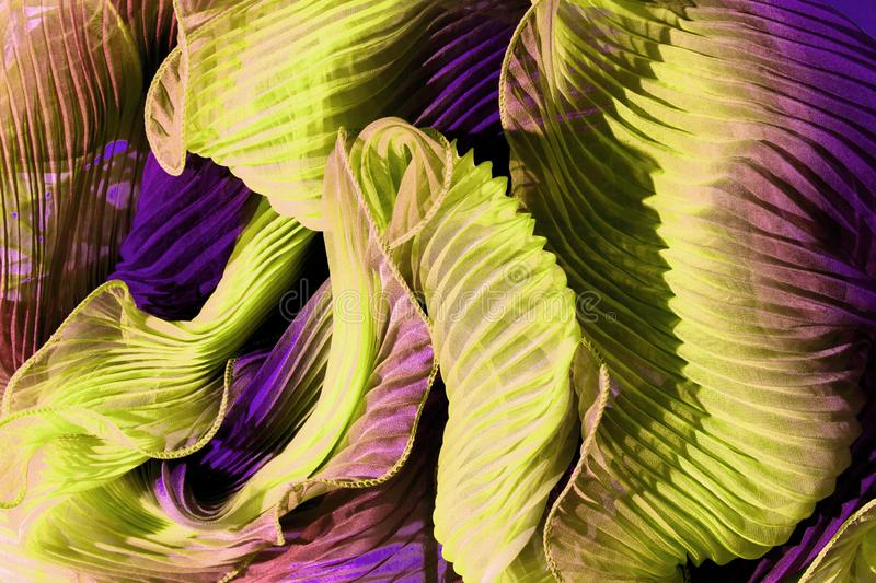 Flounces of yellow violet fabric wound by waves. stock images