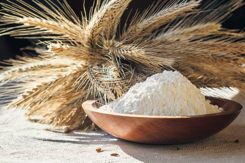 Flour с ушами пшеницы в деревянном шаре на предпосылке мешковины стоковые фотографии rf