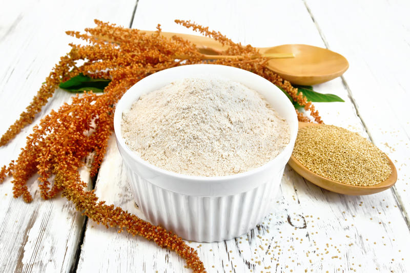 Flour amaranth in bowl with spoon and flower on board. Amaranth flour in white bowl, spoons with grain, brown flower with green leaves on a background of wooden royalty free stock photos