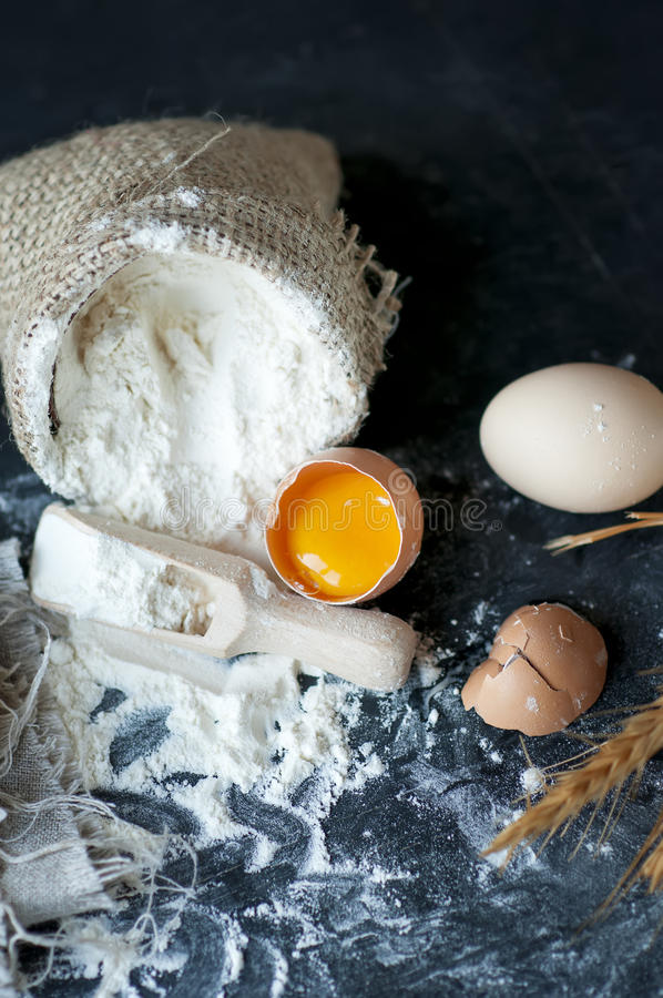 Flour in burlap with wooden spoon and eggs royalty free stock photo