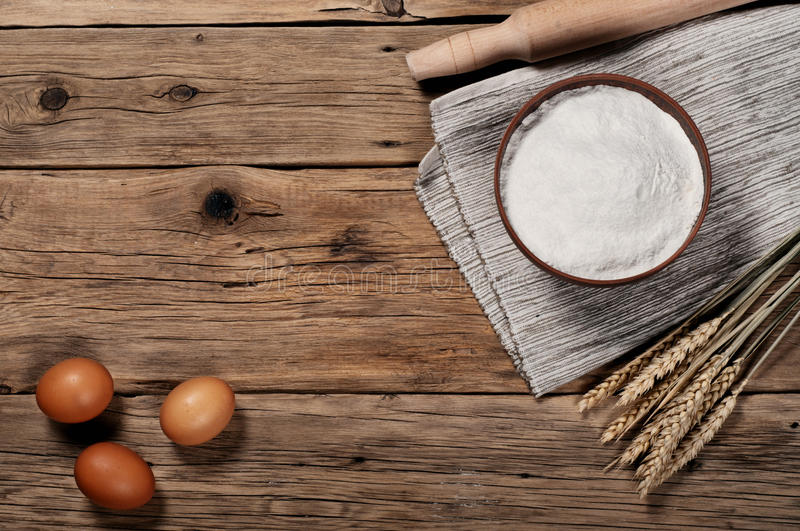 Flour, in a clay bowl with brown eggs stock photography