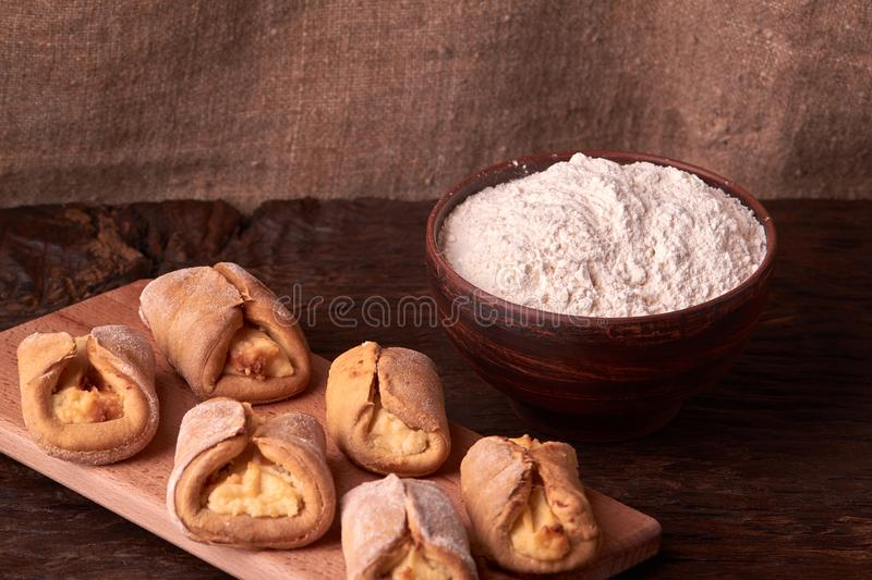 Flour in clay bowl products for making cheesecakes on a wooden chopping board. Homemade Cottage cheese cookies on black background royalty free stock photography