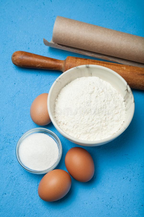 Flour, eggs, butter, sugar on a blue background, vertically.  royalty free stock images
