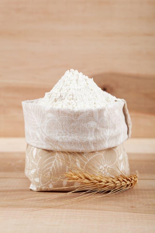 Flour em um saco da lona e em uma orelha do trigo no de madeira fotografia de stock