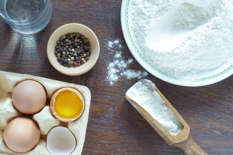 Flour em uma bacia e em uma colher de madeira Ovos da galinha imagem de stock royalty free