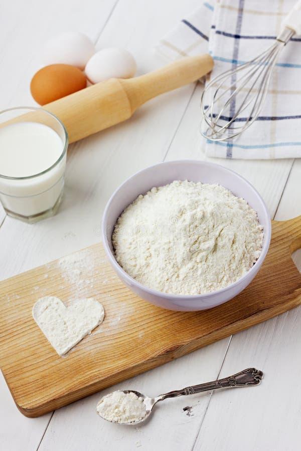 Flour en cuenco de cerámica con los huevos, la leche y el corazón de una harina foto de archivo