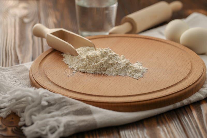 Flour en una cuchara de madera en una tabla de cortar imagen de archivo libre de regalías