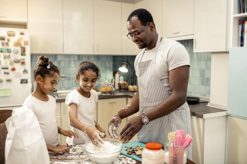 Two funny cute girls having flour on their faces while cooking pie. Flour on faces. Two funny cute dark-haired girls having flour on their faces while cooking stock photo