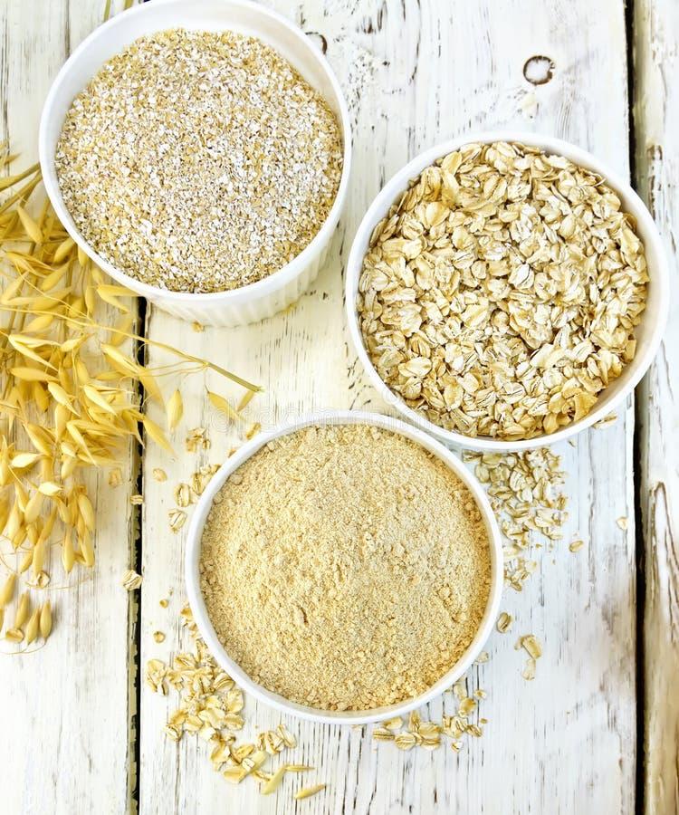 Flour l'avoine dans la cuvette blanche avec le son et les flocons à bord du dessus photographie stock