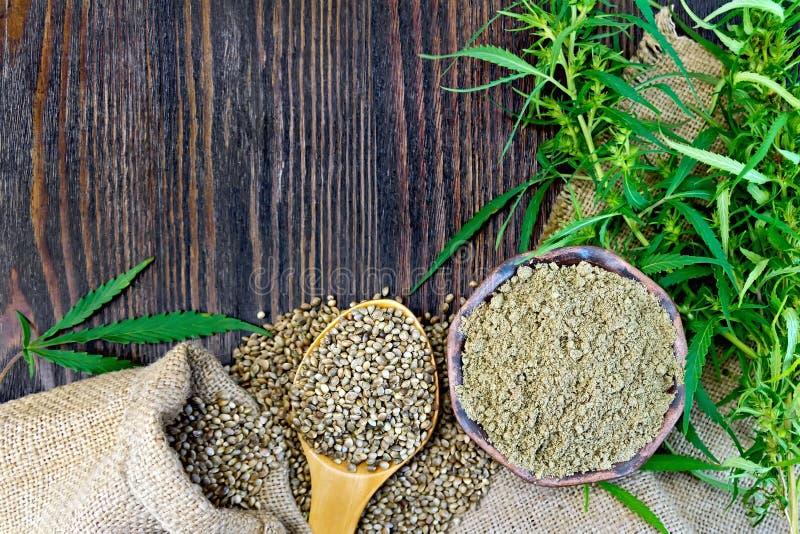 Flour le chanvre dans la cuvette et le maïs dans la cuillère sur le conseil en bois photos libres de droits