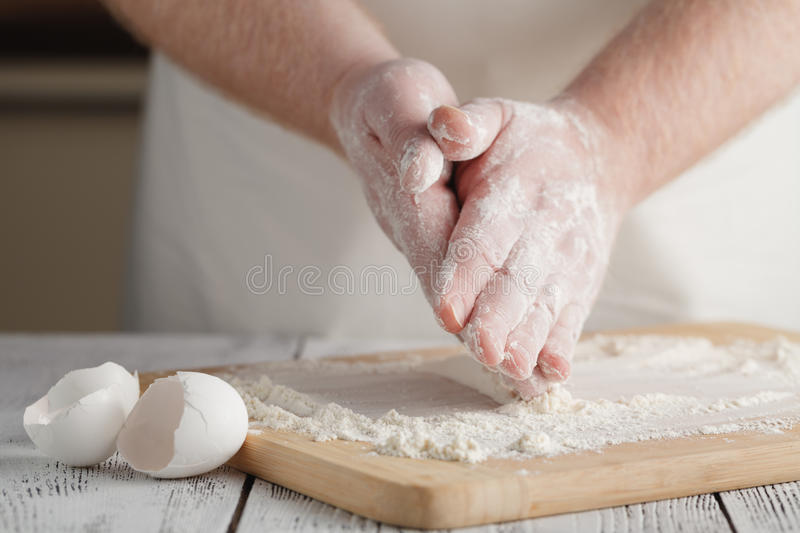 Flour on light wooden table like background with man`s hand. Sel. Ective focus stock photos
