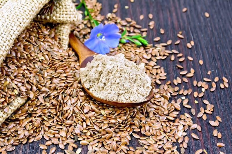 Flour o linho na colher com a flor na placa escura imagens de stock