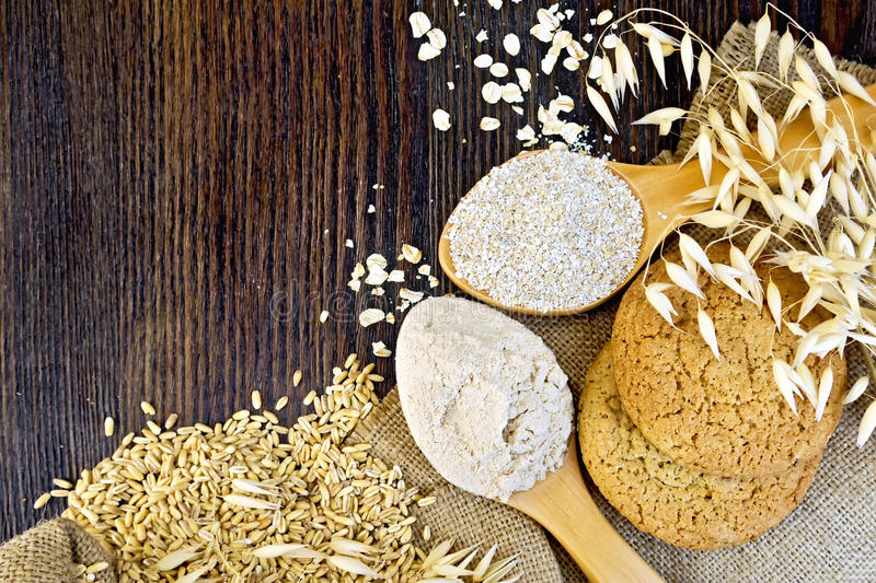 Flour oat with bran in spoons and cookies on board royalty free stock photo
