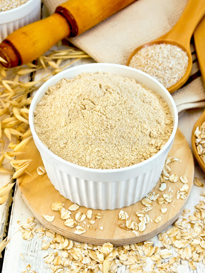 Flour oat in white bowl with bran and flakes on board stock images