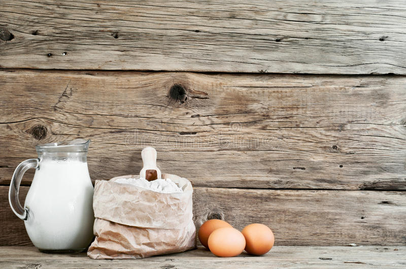 Flour in a paper bag with eggs and milk royalty free stock photo