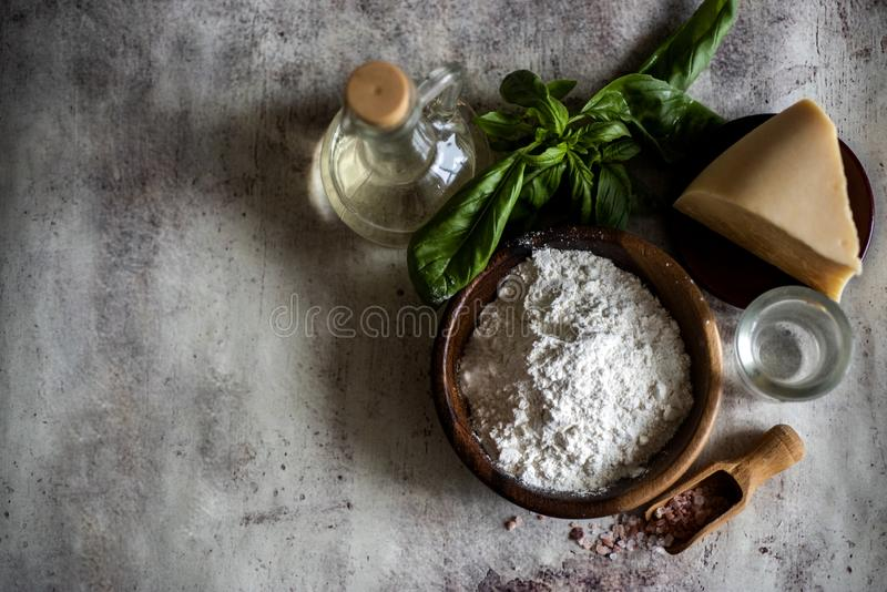 Flour on a plate, a slice of cheese, a glass of water, fresh Basil, a bottle of oil, scattered salt on an ancient gray background royalty free stock photo