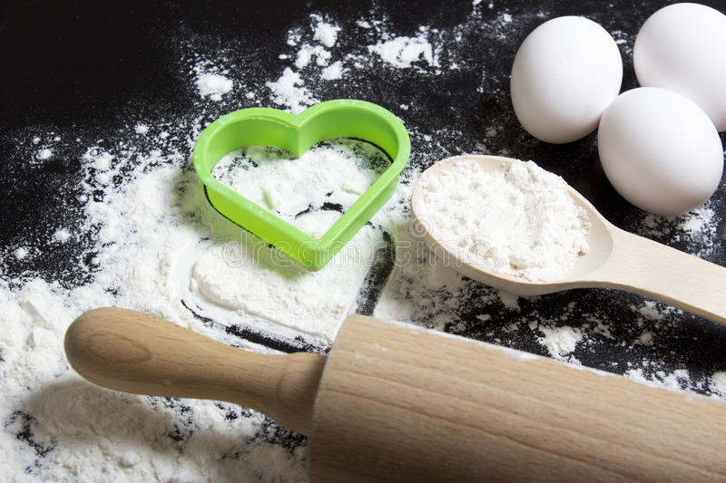 Flour and rolling pin with a heart symbol, egg. Flour on a black royalty free stock image