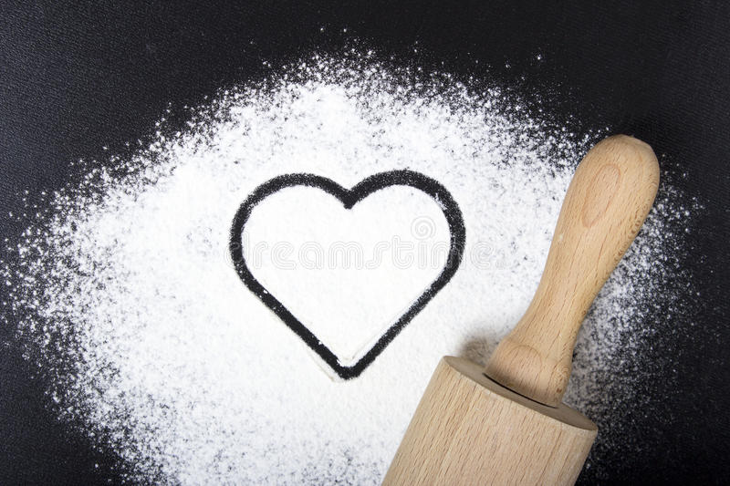 Flour and rolling pin with a heart symbol. Flour on a black back royalty free stock photos