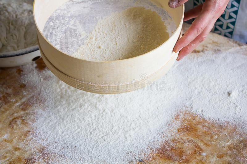 Flour is sifted through a wooden sieve. On the large white home kitchen royalty free stock photography