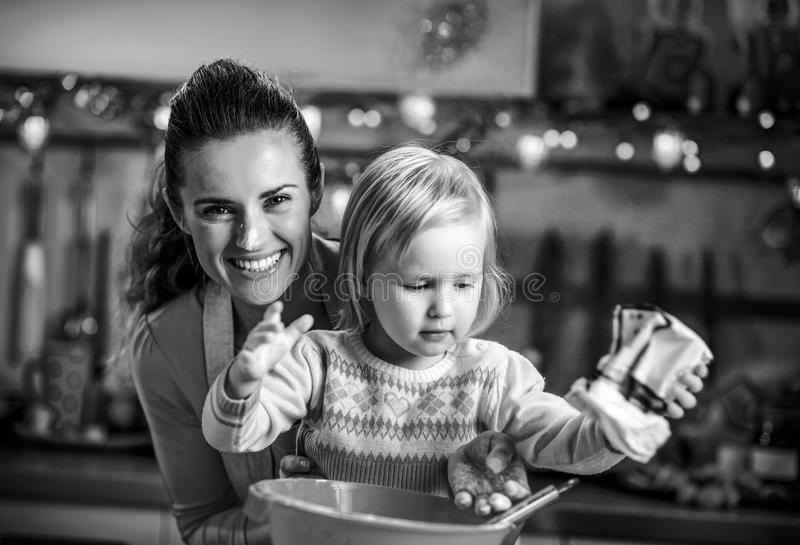 Flour smeared mother and baby making christmas cooki stock images