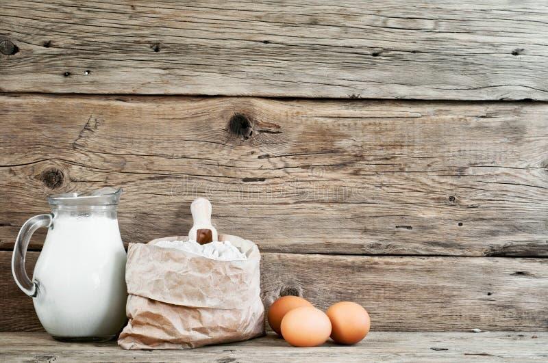 Flour in un sacco di carta con le uova ed il latte fotografia stock libera da diritti