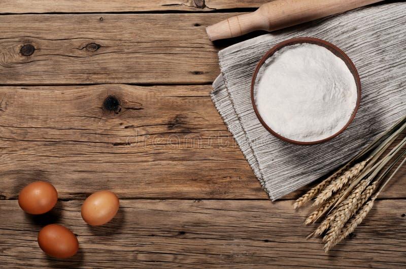 Flour, in una ciotola dell'argilla con le uova marroni fotografia stock
