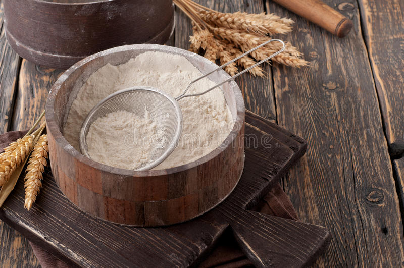 Flour in a wooden bowl with sieve on vintage board. On a dark old table, closeup. Top view with copy space royalty free stock photos