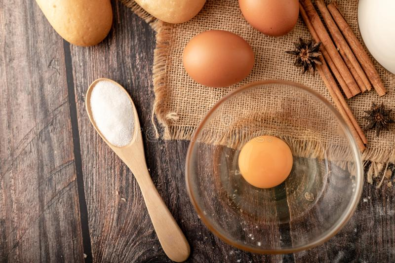 Flour in wooden spoon and eggs in bolw glass on the sack stock images