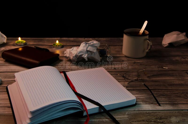 Flour of a writer, search for inspiration. A clean notebook on a wooden table with scattered crumpled paper, a mug of tea, glasses stock images