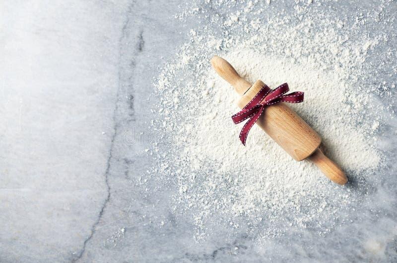 Floured мраморная рабочая поверхность и вращающая ось с красной лентой ароматичные специи gingerbread печений рождества выпечки f стоковая фотография