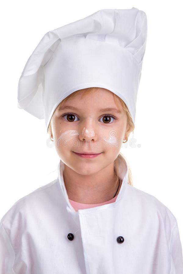 Floured face. Portrait of a cute girl chef white uniform isolated on white background stock photo